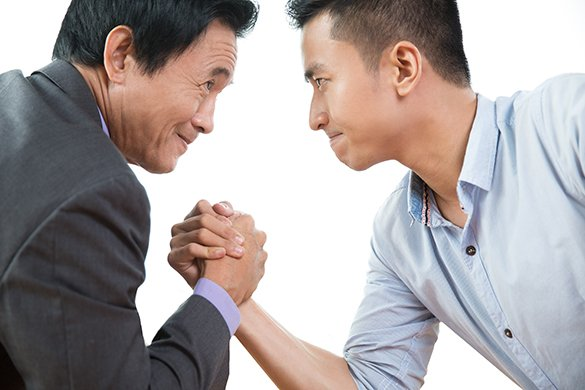 Two business men arm wrestling stubbornly