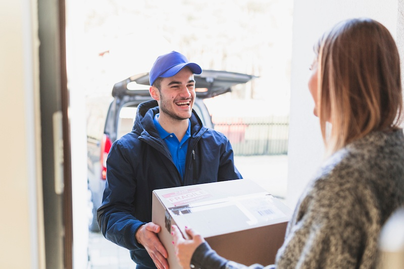Cheerful man delivering parcel to client
